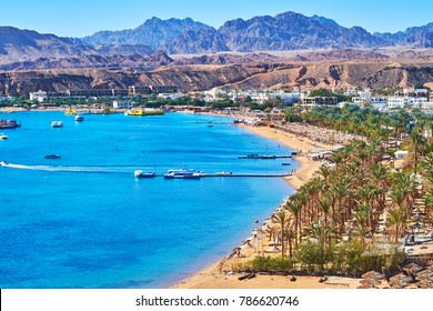 The comfortable sand beach line of El Maya bay, surrounded by giant rocky mountains, Sharm El Sheikh, Egypt.