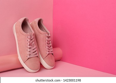 Comfortable sneakers and paper roll on color background, space for text