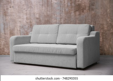 Comfortable sofa against color wall indoors