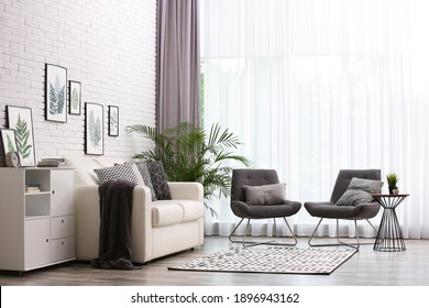 Comfortable sofa and chairs near window with elegant curtains in room