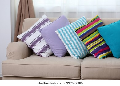 Comfortable sofa with colourful  pillows in the room, close up