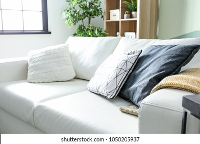 Comfortable sofa with cushions in living room