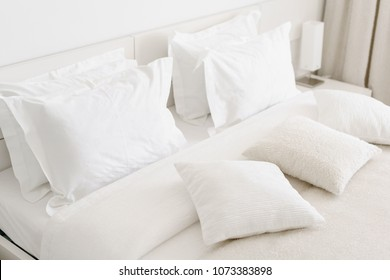 Comfortable soft pillows on the bed. Close-up white bedding sheets and pillow on light wall room background. Fresh bed concept