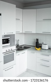 Comfortable white kitchen with a white lacquered facades. Modern kitchen clean interior design. Refrigerator, kitchen oven, microwave oven and sink. Kitchen supplies.