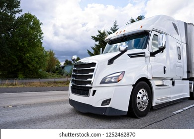 Comfortable white modern bonnet big stylish professional rig semi truck running on divided highway with dry van semi trailer for delivery commercial cargo to point of destination