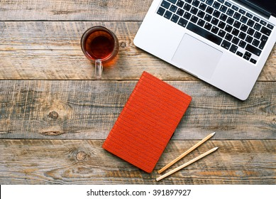 Comfortable working place, wooden table with laptop, orange notebook and cap of tea