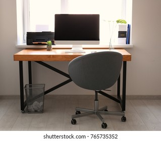 Comfortable workplace with computer monitor on table in office