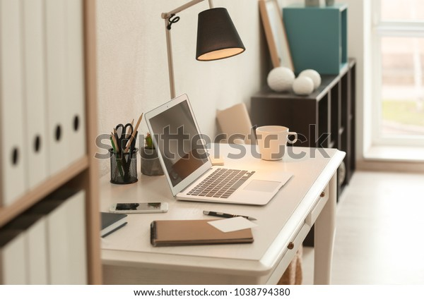 Comfortable workplace with laptop on desk