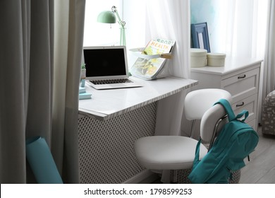 Comfortable workplace with laptop on window sill at home