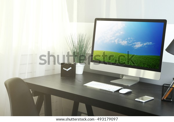 Comfortable workplace with modern computer and green spring field on screen