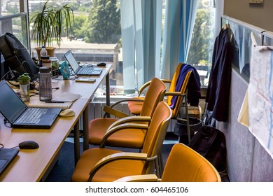 comfortable workplaces in one table with many orange armchairs and a few open laptops in front of every chair with bags on back against big window. workplaces with notebook laptops