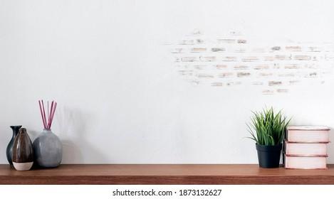 Bequeme Arbeitsfläche mit Büchern, Haustieranlage, Keramikvase und Kopienraum auf Holztisch.