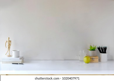 Comfortable workspace desk with books, house plant, pencils and coffee mug with copy space