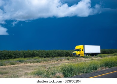 Comfortable yellow semi truck for long haul going with a cargo in dry van trailer carrying out flight on timely delivery to the customer by road passing in the middle of the California orchard plains