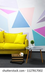 Comfortable yellow sofa against colored wall with geometrical figure.Box with books near soafa and coffee table with green plant. Relaxing zone