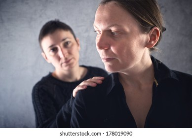 Comforting friend. Woman consoling her sad friend with hand on shoulder.
