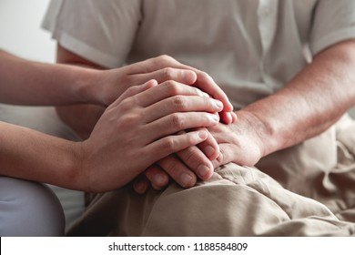 Comforting hand. Young nurse holding old man's hand. Senior care, care taker and senior retirement home service concept. Close up shot.