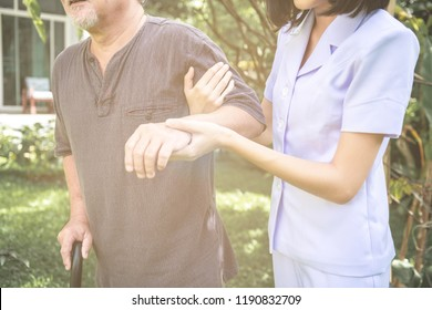 Comforting hand. Young nurse holding old man's shoulder in outdoor garden. Senior care, care taker and senior retirement home service concept.