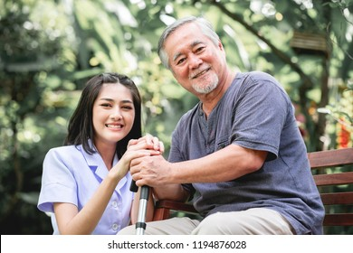 Comforting hand. Young nurse holding old man's hand in outdoor garden sitting on bench. Senior care, care taker and senior retirement home service concept.