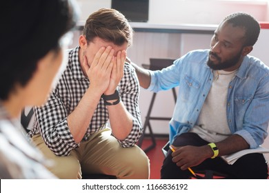 Comforting. Reliable kind black man putting his hand on the shoulder of a crying person while talking to him