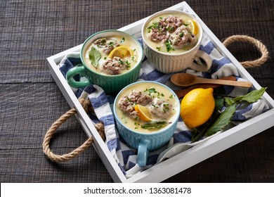 Comforting soup giouvarlakia greek meatball soup of avgolemono sauce, served in mugs with wooden spoons in a white serving tray, parsley and lemon, on an dark oak wooden background, close up