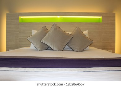 Comfy cushions and pillows on a modern hotel bed with lights illuminating the bedhead