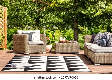 Comfy garden furniture and geometrical rug on a terrace in spa resort
