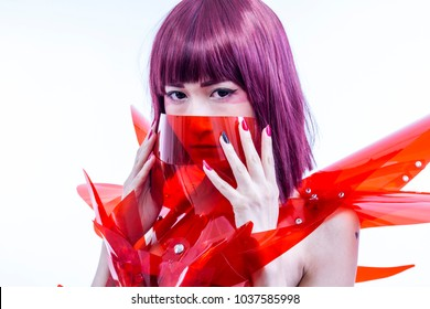 Comic Asian woman cosplayer with futuristic costume in red, made with pvc plastics and transparencies. oriental girl