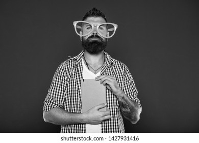 Comic and humor sense. Courses adult education. Self education concept. Literary club. Reading book as hobby. Study is fun. Hipster bearded man funny eyeglasses hold notepad or book. Read this book.