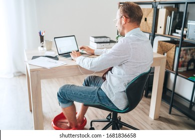 Comic modern office table situation. Businessman typing on laptop keyboard and soaring his feet in Foot hot Bath under table. Distance work in worldwide quarantine time concept image.