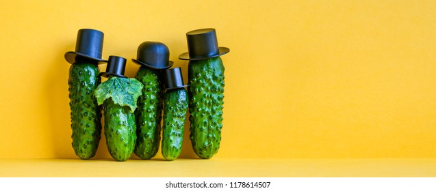 Comical green Cucumbers family on yellow background. Five funny vegetables with black old fashioned hats. Creative design food poster template. Copy space