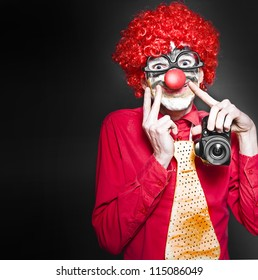 Comical Photograph Of A Smiling Clown Holding Digital Camera In A Cheesy Depiction Of A Happy Snap On Dark Studio Background