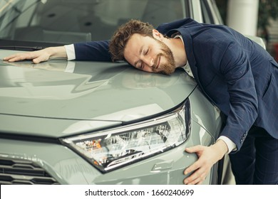 comical positive young caucasian guy hugging his new car in dealership. happy man finally gets long-awaited car, wearing formal suit