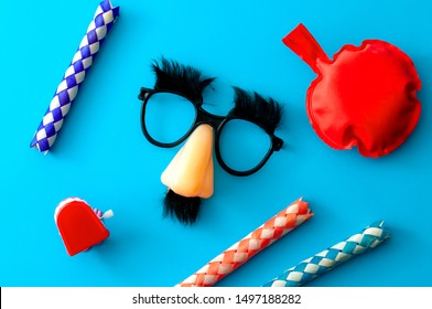 Comical prank, April fools practical joke and goofy disguise concept farting bag, chattering teeth, chinese finger trap and novelty glasses with fake nose and eyebrows isolated on blue background