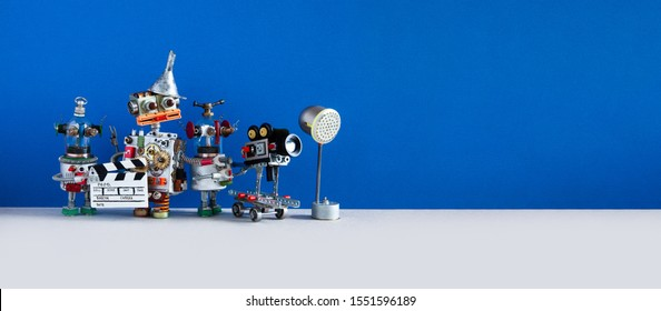 Comical robotic art filmmaking process. Backstage TV production studio with funny director cameraman and assistant. Shoots blockbuster television or movie. Copy space on blue gray backdrop