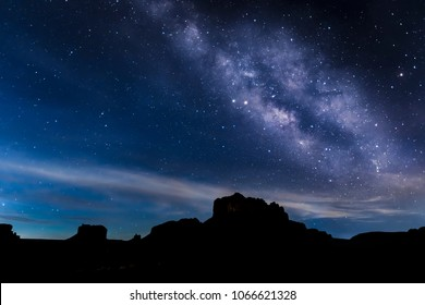 With the coming glow of sunrise silhouetting rock formations on the horizon, the Milky Way decorates the night sky over Sedona, Arizona.