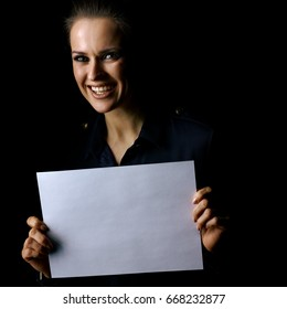 Coming out into the light. Portrait of smiling woman in the dark dress isolated on black background showing blank paper sheet