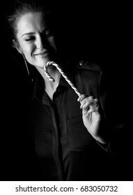 Coming out into the light. smiling woman in the dark dress isolated on black enjoying christmas candy cane