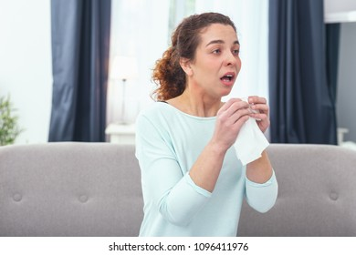 Coming up sneeze. Young fairhaired lady with her mouth open clenching to a white handkerchief being about to sneeze