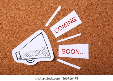 Coming Soon concept with wooden cork background.