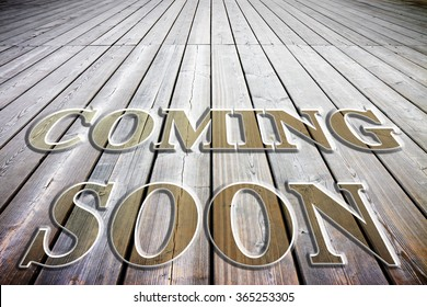 Coming soon concept written on a wooden floor slats