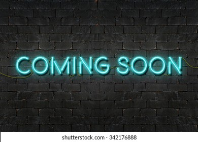 """COMING SOON"" neon sign shining on black brick wall,Business concept"