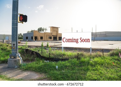 Coming Soon sign stands at the street corner/intersection, under construction convenience store is in background. Signboard with word Coming Soon and street light outdoor for brand new gas station.