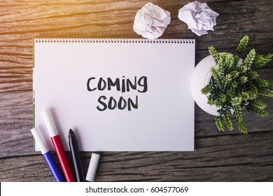 Coming Soon word with Notepad and green plant on wooden background