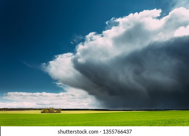 Coming Storm And Rain Above Countryside Rural Field Or Meadow Landscape With Green Grass Under Scenic Spring Blue Dramatic Sky With White Fluffy Clouds. Rain Clouds On A Sunny Day.