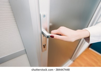 Coming to work, woman's hand opens the door