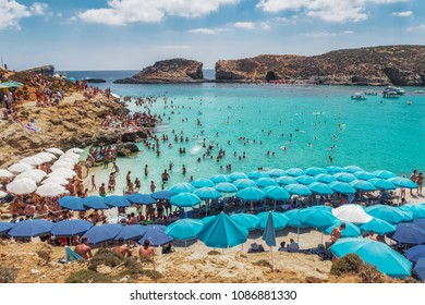Comino Island, Malta - August 03 2016: Blue Lagoon panoramic landscape with bathers and sun umbrellas. The most famous and crowded beach in Malta with crystal clear waters.