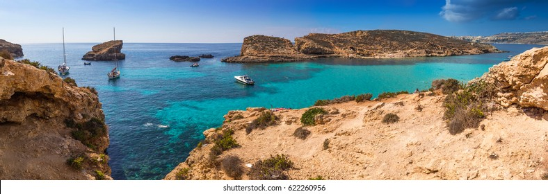 Comino, Malta - The beautiful Blue Lagoon with turquoise clear sea water, yachts and snorkeling tourists on a sunny summer day with the island of Gozo at background