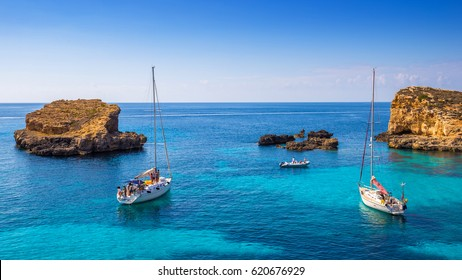 Comino, Malta - Sailing boats at the beautiful Blue Lagoon at Comino Island with turquoise clear sea water, blue sky and rocks in the water