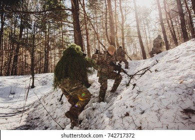 command rangers during the military operation. soldiers climbing on mountain, one of them giving hand and helping to climb. Help, support, assistance in a dangerous situation